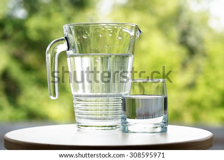 Glass of water near jug on green nature background - stock photo