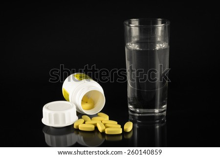 Glass of water next to the bottle of medicine - stock photo