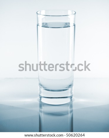 Glass of water on a reflective table top - stock photo