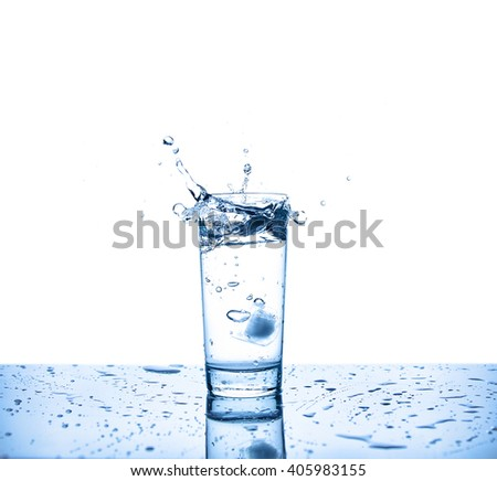 Glass of water on a table and splash - stock photo
