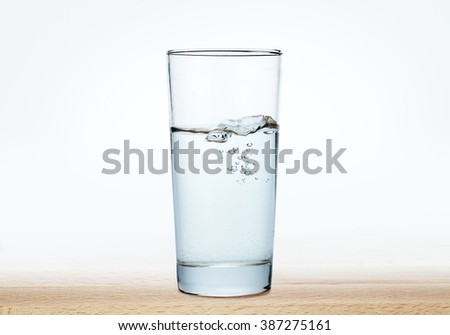 glass of water on a wood table,water in glass on  wood - stock photo