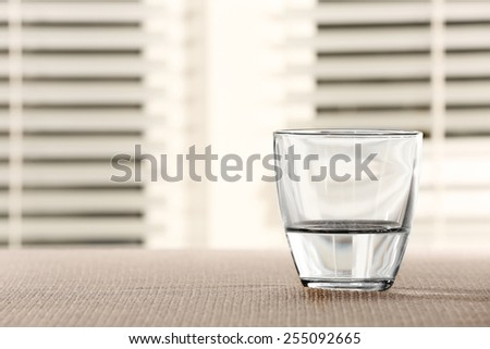 Glass of water on table on light background - stock photo