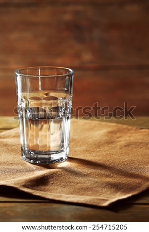 Glass of water on table on wooden background - stock photo