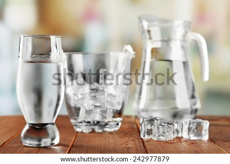 Glass of water with ice and bucket on wooden table and light blurred background - stock photo