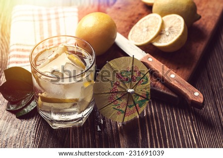 glass of water with ice and lemon on wooden table - stock photo