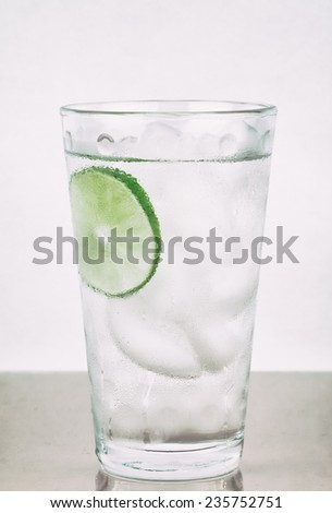 Glass of water with ice and slice of lime, and condensation. Gritty processing. - stock photo