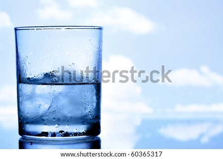 Glass of water with ice, blue sky in the background