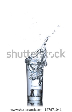 Glass of water with ice cubes on white background. Water splash