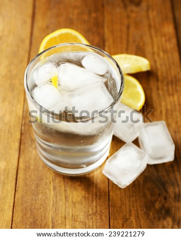 Glass of water with ice cubes on wooden table - stock photo