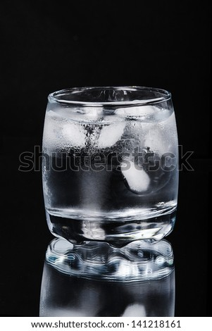 Glass of water with ice on a black background - stock photo