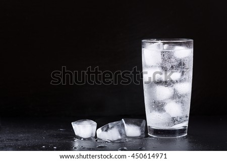 glass of water with ice on dark background - stock photo