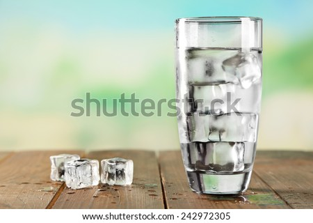 Glass of water with ice on wooden table and light blurred background - stock photo