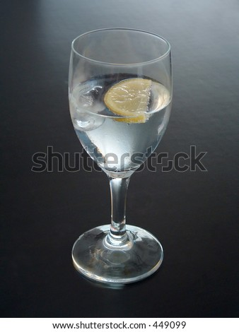 glass of water with lemon on black background - stock photo