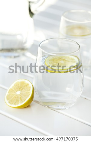 Glass of water with lemon on white background