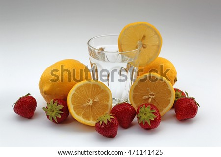 Glass of water with lemon surrounded by lemons and strawberries on white background