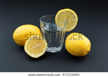 Glass of water with lemon surrounded by lemons on black background