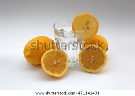 Glass of water with lemon surrounded by lemons on white background