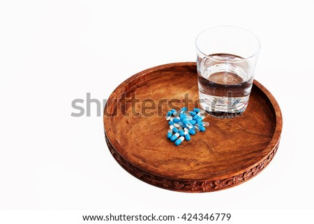 glass of water with medicines in capsules on wooden tray - stock photo