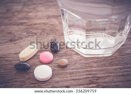 glass of water with medicines on wood background - stock photo