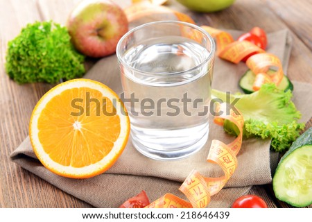 Glass of water with vegetables and measuring tape on table close-up - stock photo