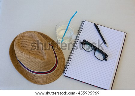 Glass of water with writing materials pen and note book