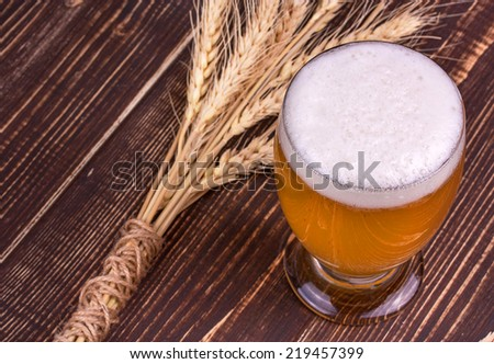 Glass of wheat beer and ears - stock photo