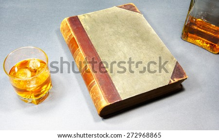 glass of whiskey, a bottle and a book on a gray background - stock photo