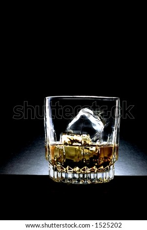 Glass of whiskey against black background. - stock photo