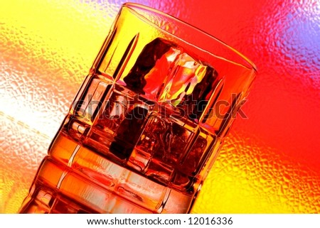 Glass of whiskey against multi colored abstract background. - stock photo