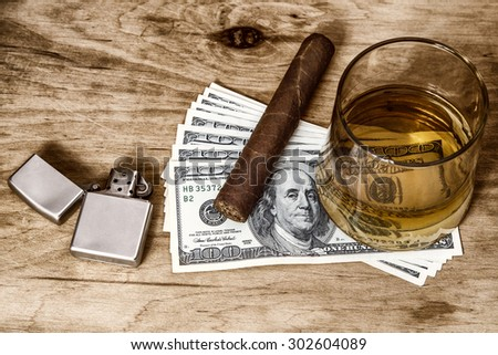 Glass of whiskey and a money with cuban cigar and lighter on a wooden table. - stock photo