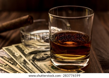 Glass of whiskey and a money with cuban cigar on a wooden table. Angle view, shallow depth of field, focus on the glass of whiskey - stock photo