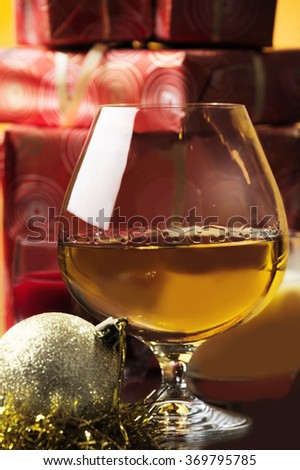 glass of whiskey and Christmas gifts and Christmas decoration at the background - stock photo