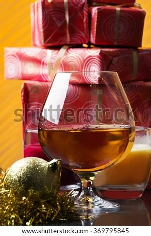 glass of whiskey and Christmas gifts and Christmas decoration at the background