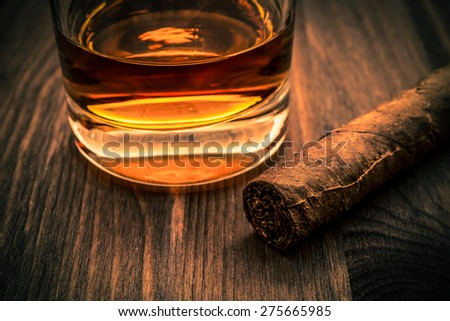 Glass of whiskey and cuban cigar on a wooden table. Focus on the cuban cigar, image vignetting and the orange-blue toning