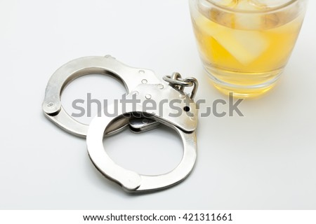 Glass of whiskey and handcuffs - Drinking law concept - stock photo
