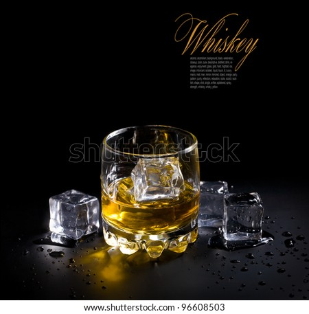 glass of whiskey and ice  over a black background - stock photo