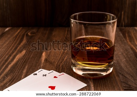 Glass of whiskey and playing cards on the wooden table. Angle view, identification cards ace Russian letter - stock photo