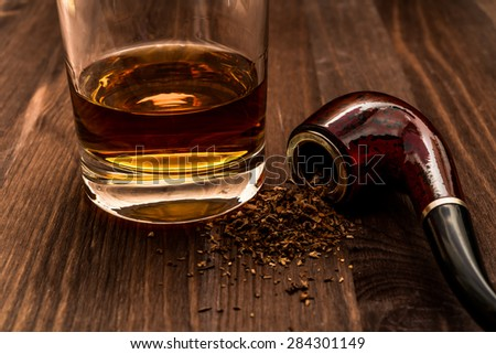 Glass of whiskey and tobacco pipe with tobacco leaves are scattered on the wooden table