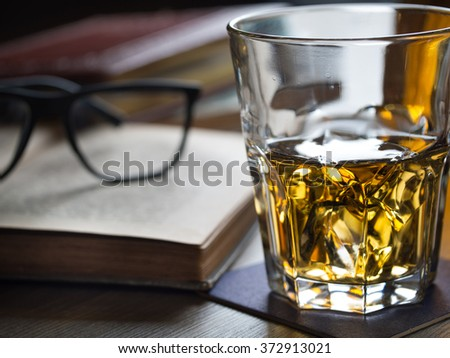 Glass of whiskey on a table with books, cigar and spectacles - stock photo