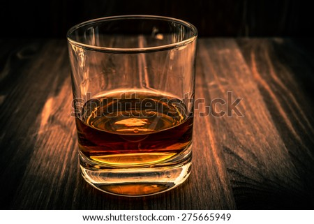 Glass of whiskey on a wooden table. Angle view, image vignetting and the orange-blue toning