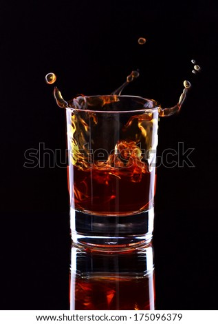 Glass of whiskey on dark background, selective focus on the glass - stock photo