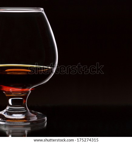 Glass of whiskey on dark background, selective focus on the glass, with place for text - stock photo