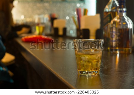 Glass of whiskey on ice on a bar counter, close up view with people blurred in the background drinking at the pub - stock photo
