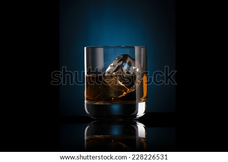 Glass of Whiskey on the Rock with Ice Cubes - stock photo