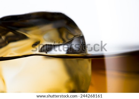 Glass of Whiskey on the Rock with Ice Cubes. Shallow Depth of Field - stock photo