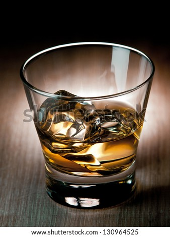 Glass of whiskey on the rocks - stock photo