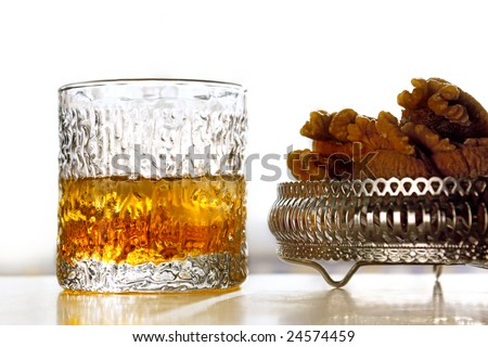glass of whiskey on the rocks and appetizer of figs and nuts - stock photo