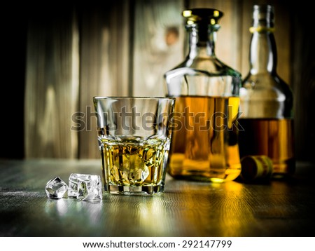 Glass of whiskey on the rocks and two bottles on a wooden background - stock photo
