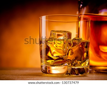 Glass of whiskey on the rocks next to a bottle - stock photo