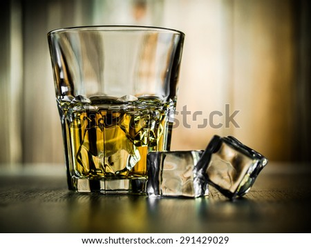 Glass of whiskey on the rocks on a wooden background - stock photo